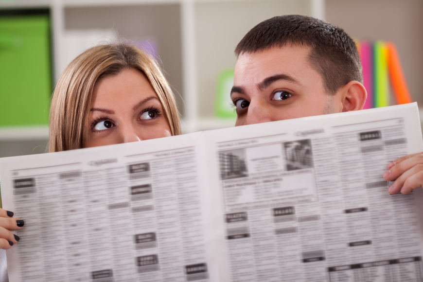 Couple peeping behind a newspaper