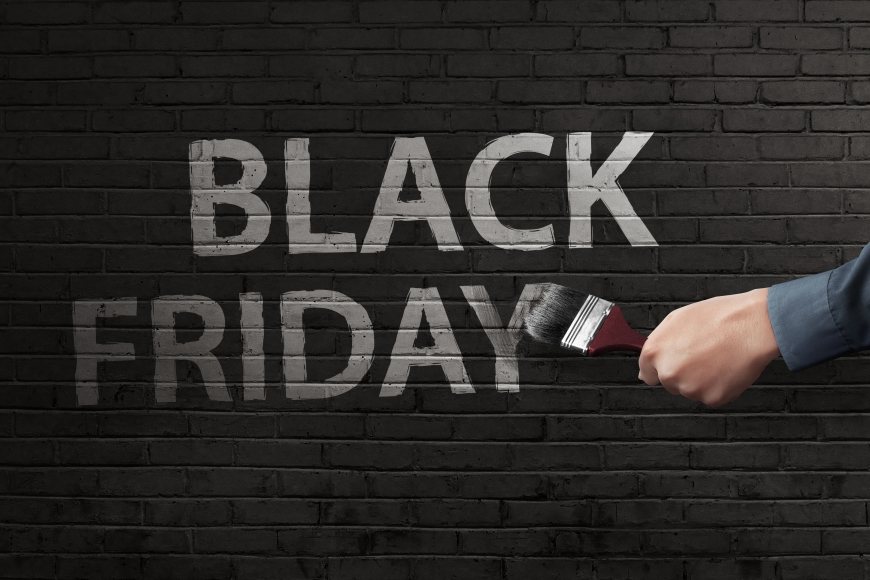 Man hand writing white Black Friday text with brush on the bricks wall